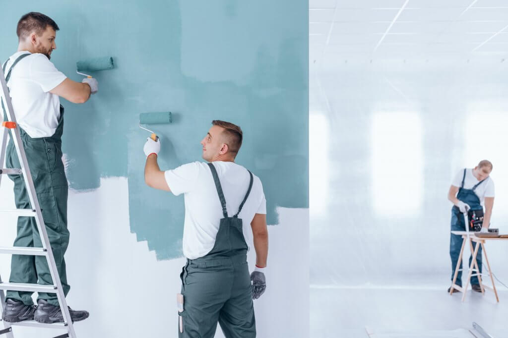 Men painting empty home interior